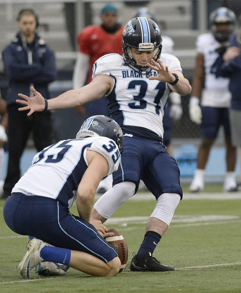 """With teammate Derek Deoul holding, University of Maine kicker Kenny Doak attempts a field goal in a game last spring in Orono. Last season's demotion """"definitely lit a fire under my butt,"""" says Doak, who struggled in his freshman year. """"I'm a competitive kid and I don't like to sit on the sidelines and watch other people do what I can do. I took it as an initiative to work really hard last offseason."""""""