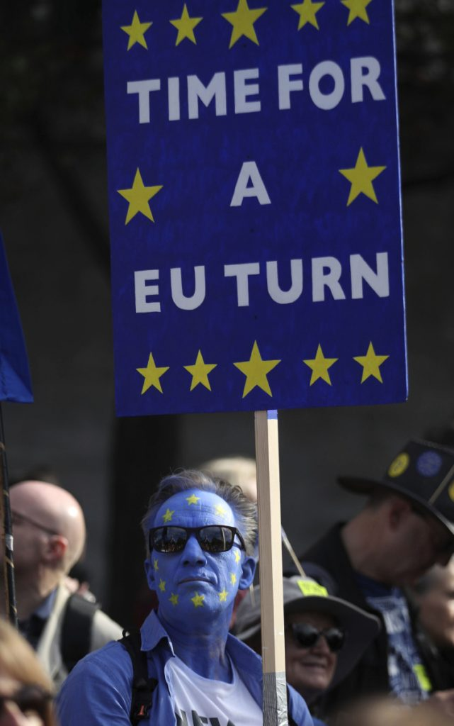 An anti-Brexit campaigner, with his face painted in the colors of the European Union flag, marches in London.