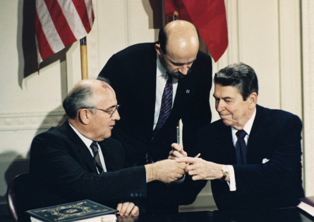 President Ronald Reagan and Soviet leader Mikhail Gorbachev exchange pens during the Intermediate Range Nuclear Forces Treaty signing ceremony on Dec. 8, 1987, at the White House. Gorbachev's translator Pavel Palazhchenko stands in the middle.