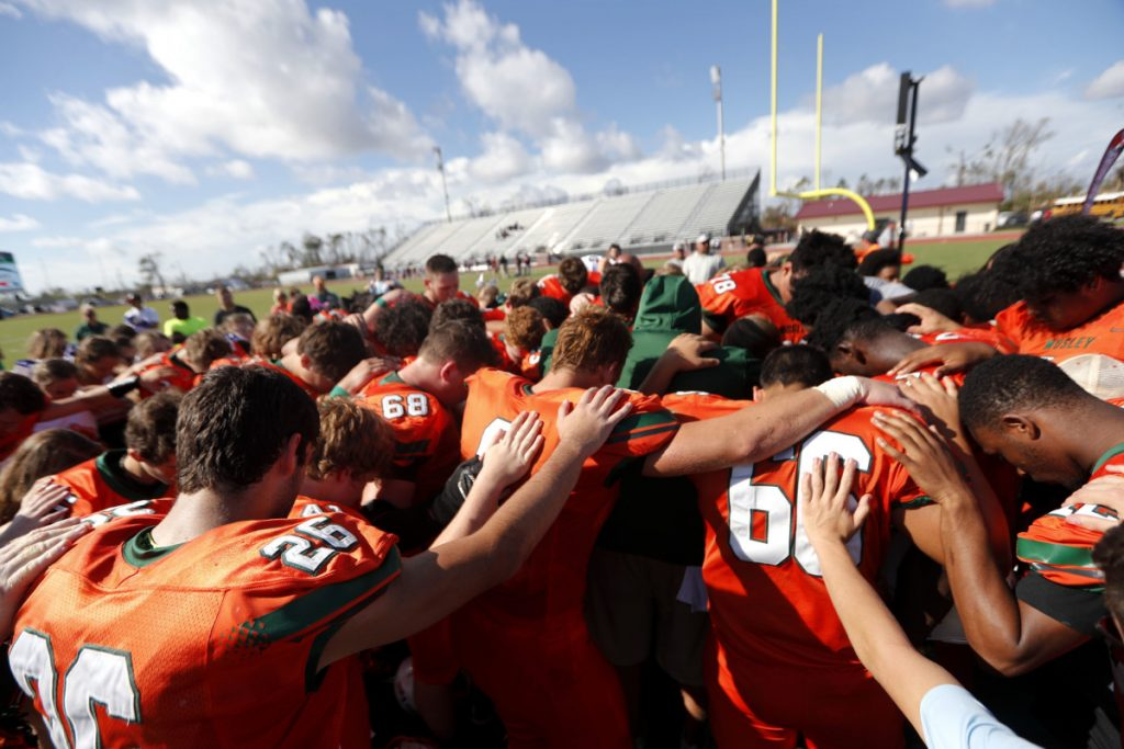 Coaches and players from Mosley High pray together after their loss Saturday to Pensacola High, in the aftermath of Hurricane Michael in Panama City, Fla.