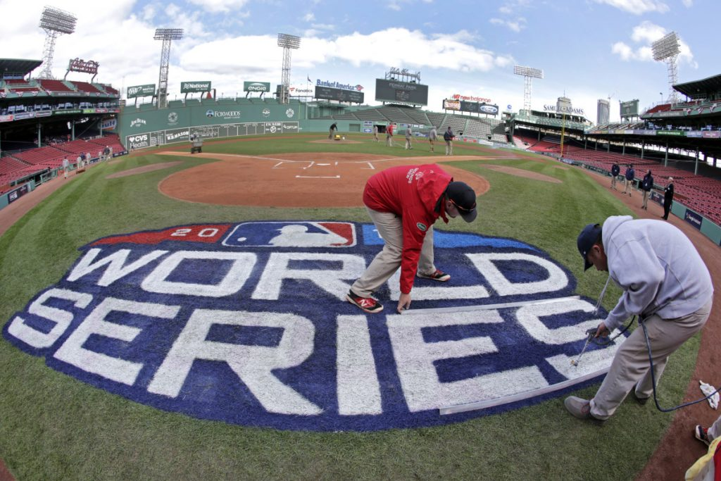 Grounds crew members paint the World Series logo behind home plate at Fenway Park on Sunday as they prepare for Game 1 of the World Series between the Boston Red Sox and the Los Angeles Dodgers on Tuesday.