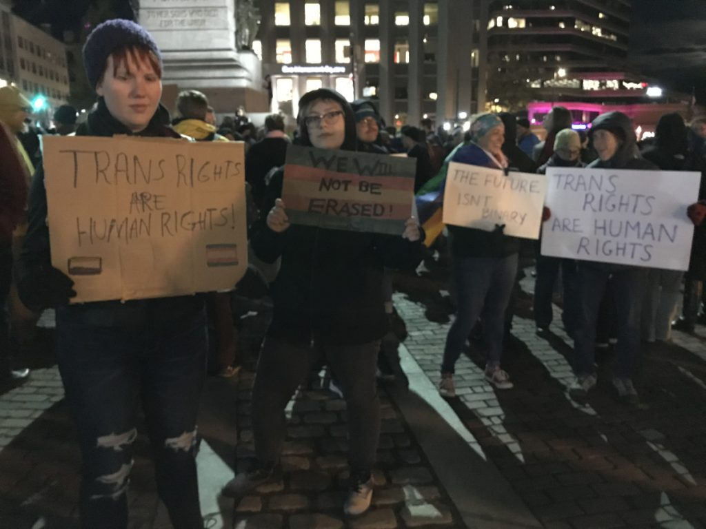 Kat Pyburn of Westbrook, left, and Elliott Babcock of Portland, center, join more than 300 other people supporting transgender rights during a protest in Monument Square on Wednesday night.