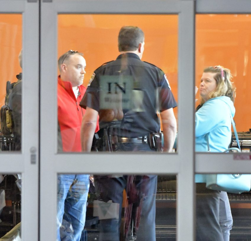 A police officer with the Louisville Metro Police Department interviews customers following a shooting that left two people dead and a suspect in custody at a Kroger grocery, Wednesday, Oct. 24, 2018, in Jeffersontown, Ky. A man fatally shot another man inside a Kroger grocery store, shot and killed a woman in the parking lot, and then exchanged fire with an armed bystander who intervened before he fled the scene on the outskirts of Louisville, Kentucky, on Wednesday, police said. He was captured shortly afterward. (AP Photo/Timothy D. Easley)