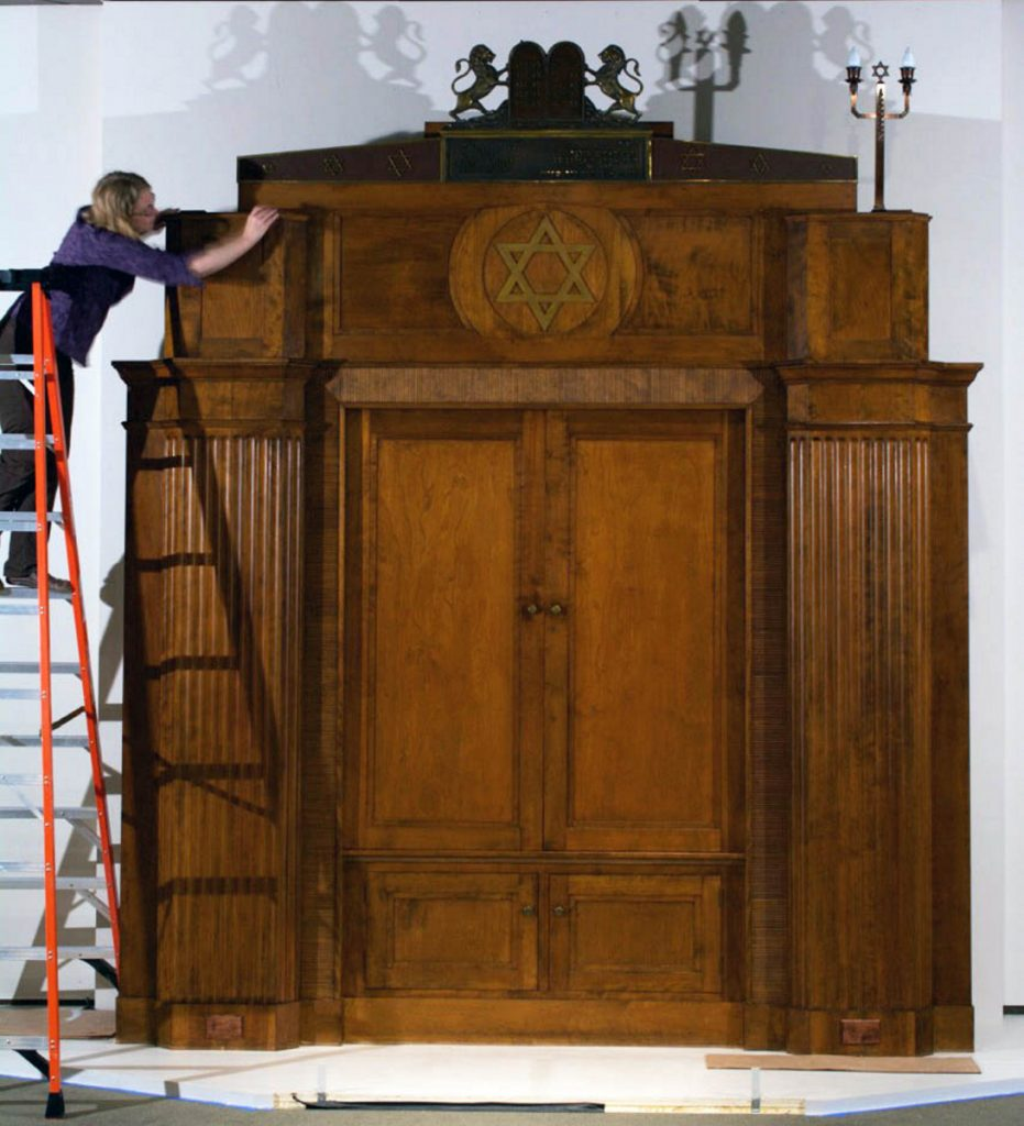 "Maine State Museum objects conservator Teresa Myers makes final adjustments to the trim of the 1930s Torah ark once in the former Beth Abraham Synagogue in Auburn. The ark was meticulously disassembled and moved to the Maine State Museum for ""Maine + Jewish: Two Centuries."""