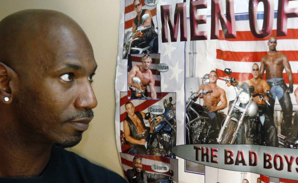 Former male dancer David Crosby looks at a poster showing Cesar Sayoc, second from bottom and at right on motorcycle next to Crosby, on Saturday in Hopkins, Minnesota. Sayoc was identified by authorities as the Florida man who allegedly sent pipe bombs to some of President  Trump's most prominent critics. Crosby said he worked with Sayoc about 12 years ago.