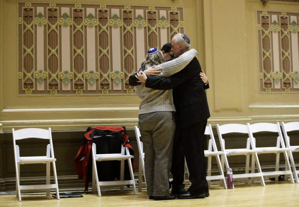Rabbi Jeffrey Myers, right, of Tree of Life/Or L'Simcha Congregation hugs Rabbi Cheryl Klein, left, of Dor Hadash Congregation and Rabbi Jonathan Perlman during a community gathering Sunday that was held in the aftermath of a deadly shooting at the Tree of Life synagogue in Pittsburgh.