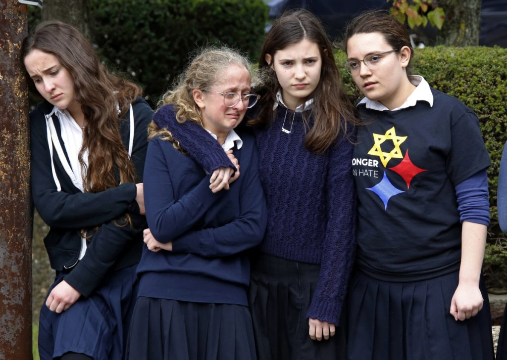 Students from the Yeshiva School in the Squirrel Hill neighborhood of Pittsburgh pay their respects as the funeral procession for Dr. Jerry Rabinowitz passes their school en route to Homewood Cemetery after a service at the Jewish Community Center on Tuesday. Rabinowitz was one of the people killed while worshipping at the Tree of Life synagogue on Saturday.