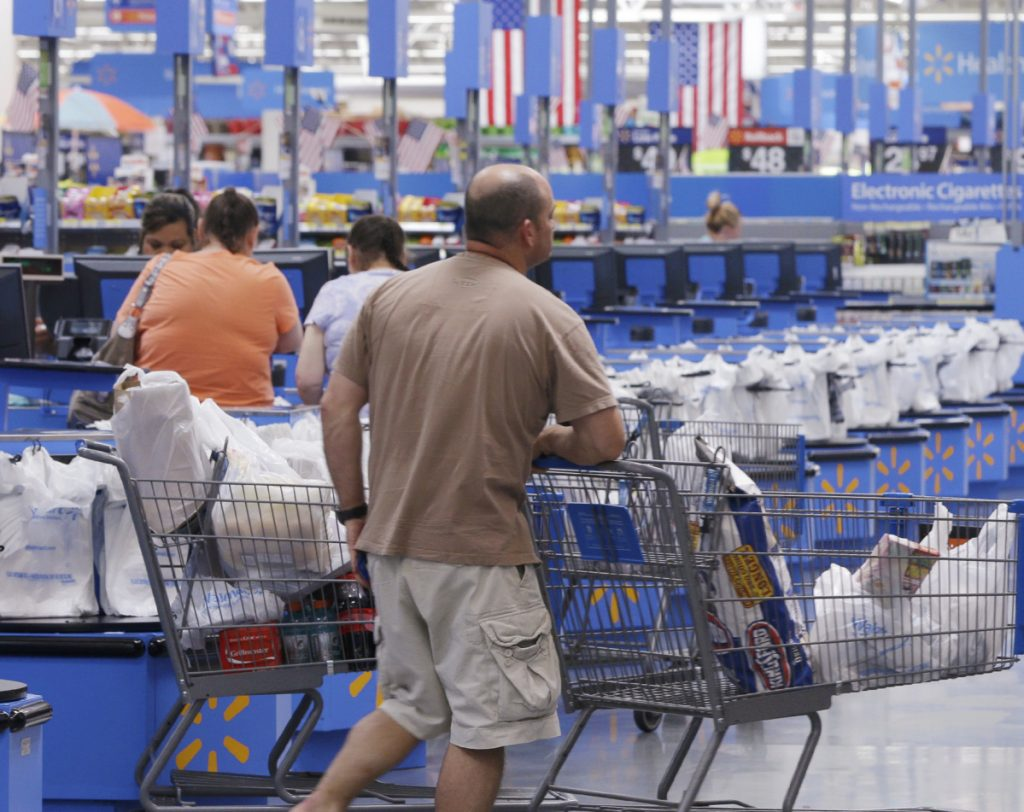 A shoppers head for a checkout at the Walmart Supercenter store in Springdale, Ark. In an effort to speed up checking out, Walmart is enabling clerks to process purchases in busy store aisles.