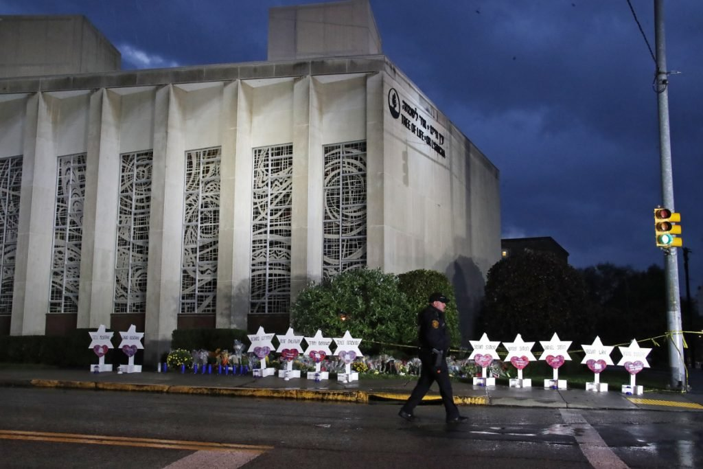 A Pittsburgh Police officer walks past the Tree of Life Synagogue and a memorial of flowers and stars on Oct. 28.