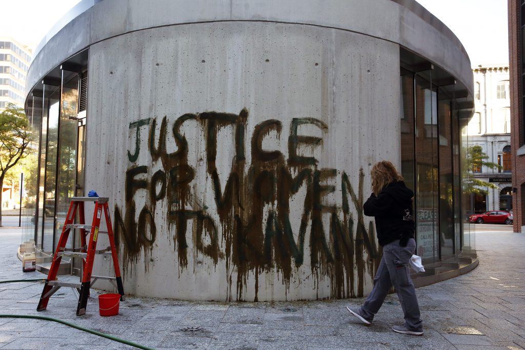 A woman, who declined to give her name, works to remove graffiti from a building near U.S. Sen. Susan Collins' downtown Portland office on Friday morning.