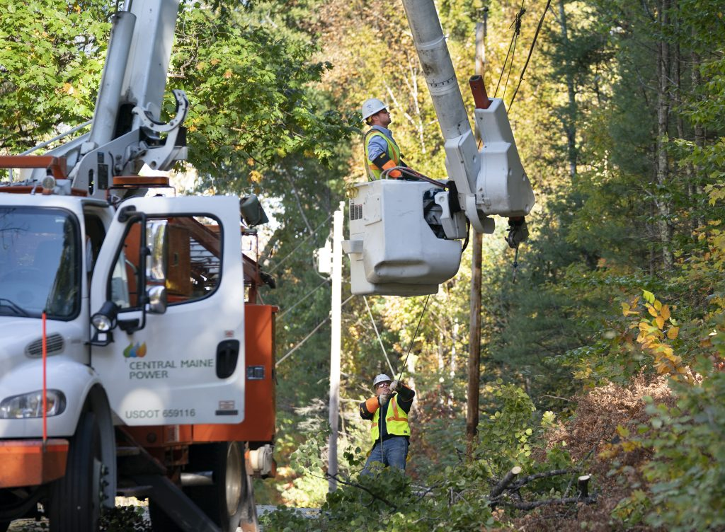 Andrew VanDecker, in bucket, and Paul Reynolds, both linemen with Central Maine Power, work on a power line that had a tree fall on it on Conesca Road in Raymond on Tuesday.