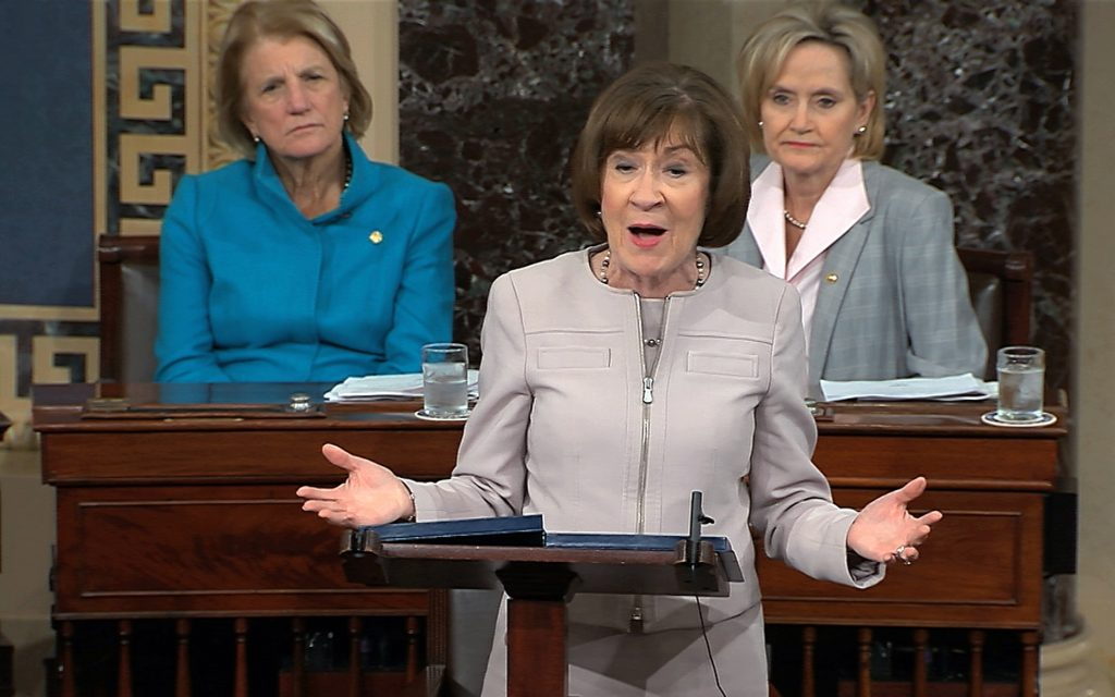 In this image from video provided by Senate TV, Sen. Susan Collins, R-Maine., speaks on the Senate floor about her vote on Supreme Court nominee Judge Brett Kananaugh, Friday, Oct. 5, 2018 in the Capitol in Washington.  Sen Shelly Capito, R-W.Va., sits rear left and Sen. Cindy Hyde-Smith, R-Miss., sits right.