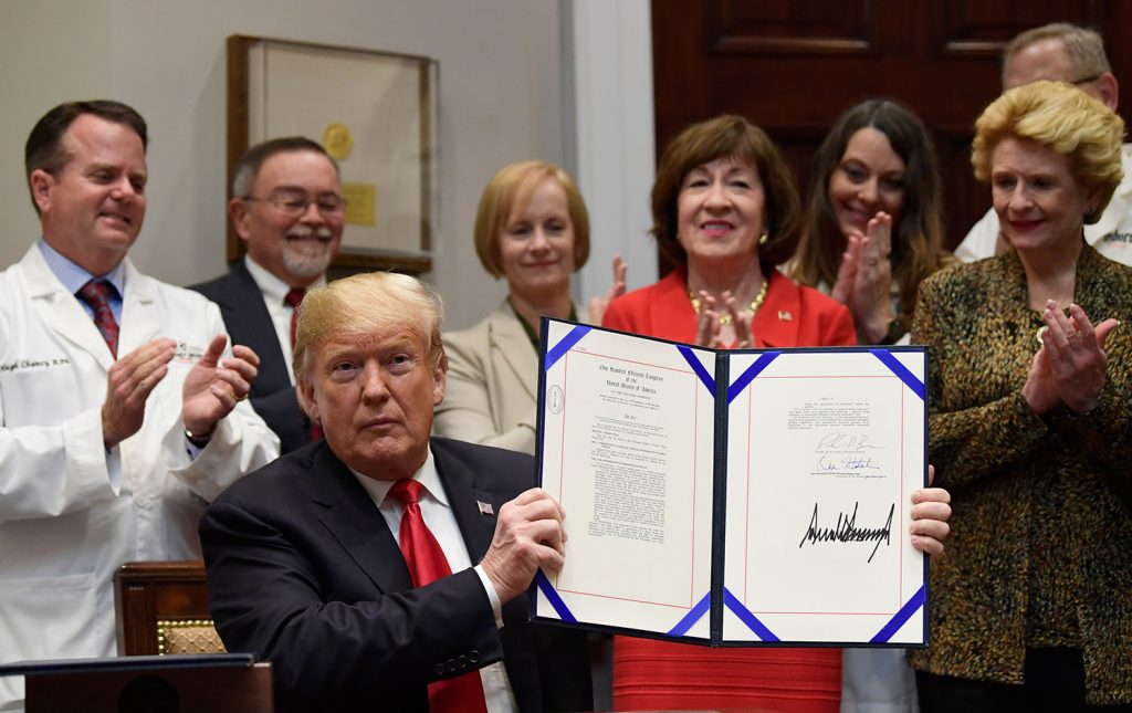 """President Trump holds up the """"Patient Right to Know Drug Prices Act"""" after signing it and the """"Know the Lowest Price Act of 2018,"""" during a ceremony at the White House in Washington on Wednesday. The bills, which were sponsored by Sen. Susan Collins, R-Maine, at rear, and Sen. Debbie Stabenow, D-Mich., right, help protect Medicare patients and those with private insurance from overpaying for prescription drugs by outlawing pharmacy """"gag clauses."""""""