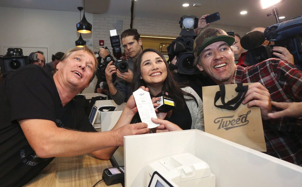 Canopy Growth CEO Bruce Linton, left to right, poses with the receipt for the first legal cannabis for recreation use sold in Canada to Nikki Rose and Ian Power at the Tweed shop on Water Street in St. John's N.L. at 12:01 am NDT on Wednesday.