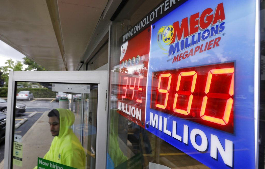The Mega Millions jackpot is displayed as a customer leaves the Corner Market, Wednesday, in Lyndhurst, Ohio. The next drawing will be Friday.