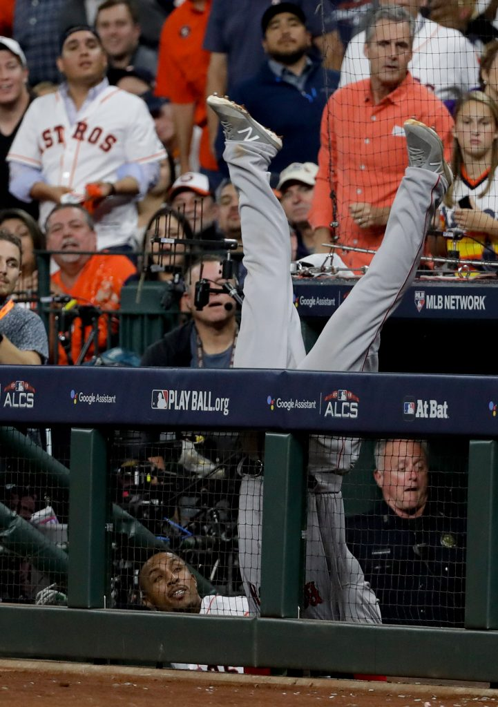 Red Sox first baseman Steve Pearce falls into the Houston dugout trying to catch a foul ball hit by the Astros' Josh Reddick in the seventh inning.
