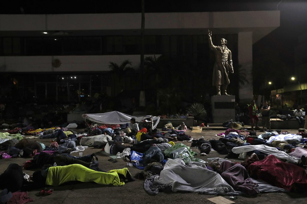 Honduran migrants hoping to reach the U.S. sleep in the southern Mexico city of Tapachula, Monday, Oct. 22, 2018, in a public plaza featuring a statue of Mexican national hero Miguel Hidalgo, a priest who launched Mexico's War of Independence in 1810. Keeping together for strength and safety in numbers, some huddled under a metal roof in the city's main plaza Sunday night.