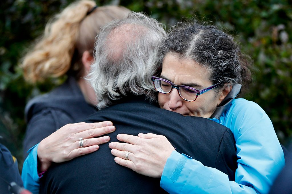 People embrace along the street in the Squirrel Hill neighborhood of Pittsburgh where a shooter opened fire during services at the Tree of Life Synagogue on Saturday.
