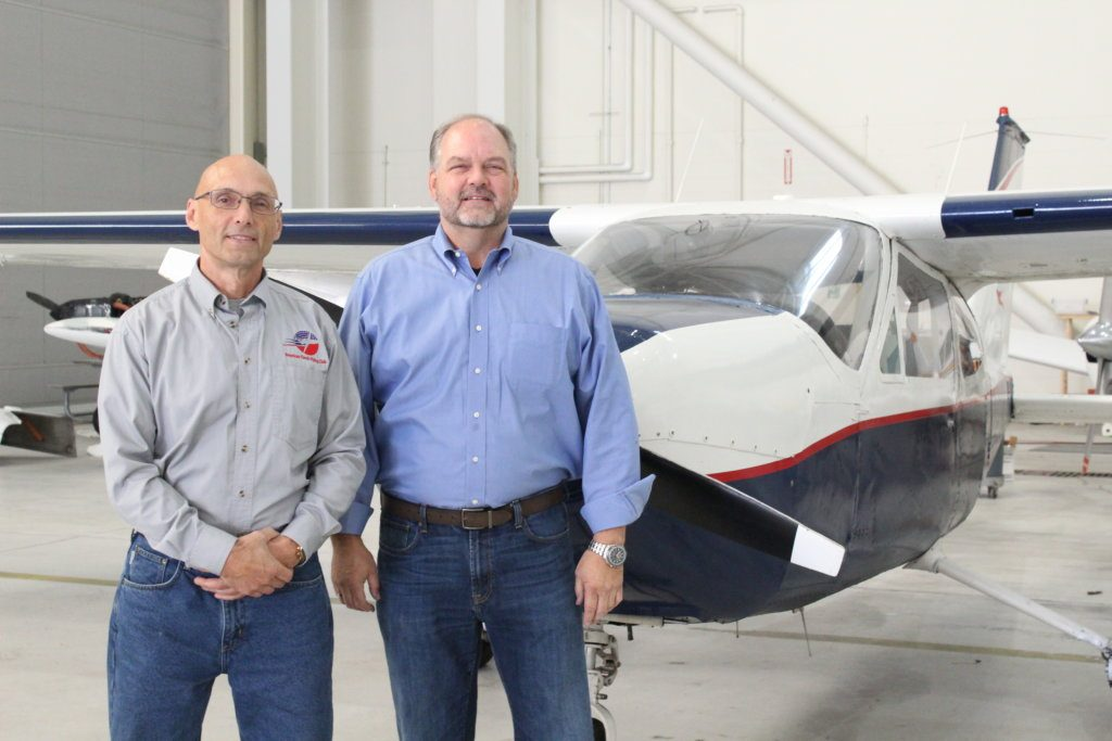 "John Favreau, left, and David Keen of American Classic Flying Club stand with a Cesna Cardinal 177. Keen, who owns American Classic Aviation, said he and his instructors want to reach out to more young people to get them interested in flying careers. ""It's a growth industry."""
