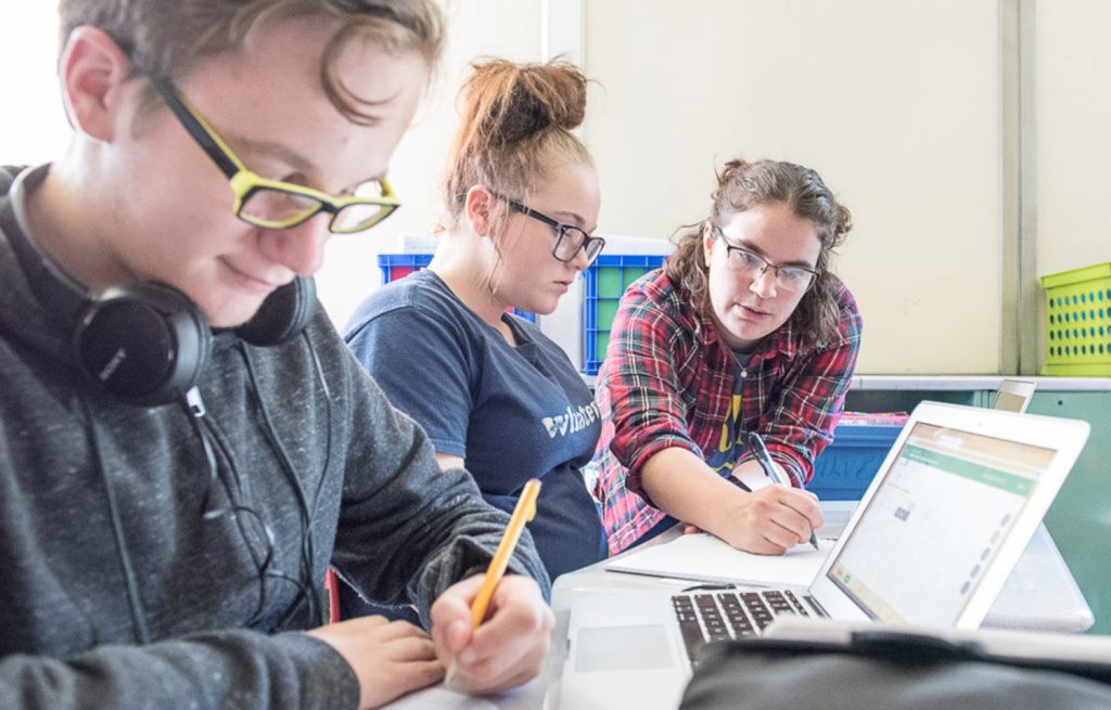 Noah Tirado works on an equation while freshman math teacher Ursula Cote, right, helps Zoe Collins on an assignment in math class at Edward Little High School in Auburn on Wednesday. The school has returned to a traditional grading system.