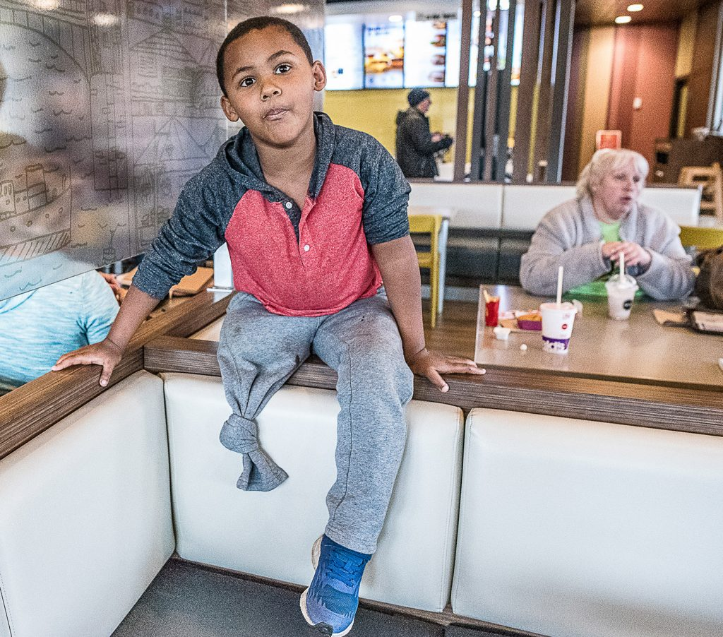 Adam Mattson, 5, was struck by a bucket loader last year and lost both of his legs. Doctors were able to reattach his left leg. His mother, Kim Mattson, sits behind him, at right, in the Farmington McDonald's restaurant Wednesday.