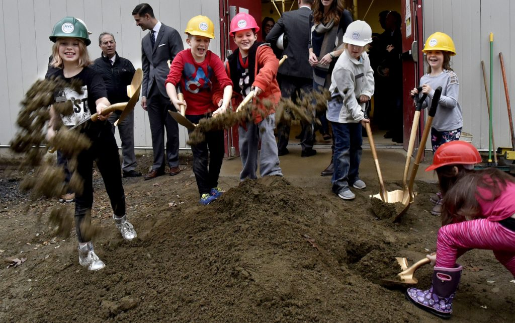 From left, Lilly Howe, Angus Johnson, Nikolai Fay, Silver Picard, Juliet Boivin and Isabella Veilleux take an active part in the groundbreaking ceremony for the Alfond Youth Center Wellness project, scooping up dirt and flinging it toward the photographer after speeches by contributors to the $6.12 million project on Thursday.