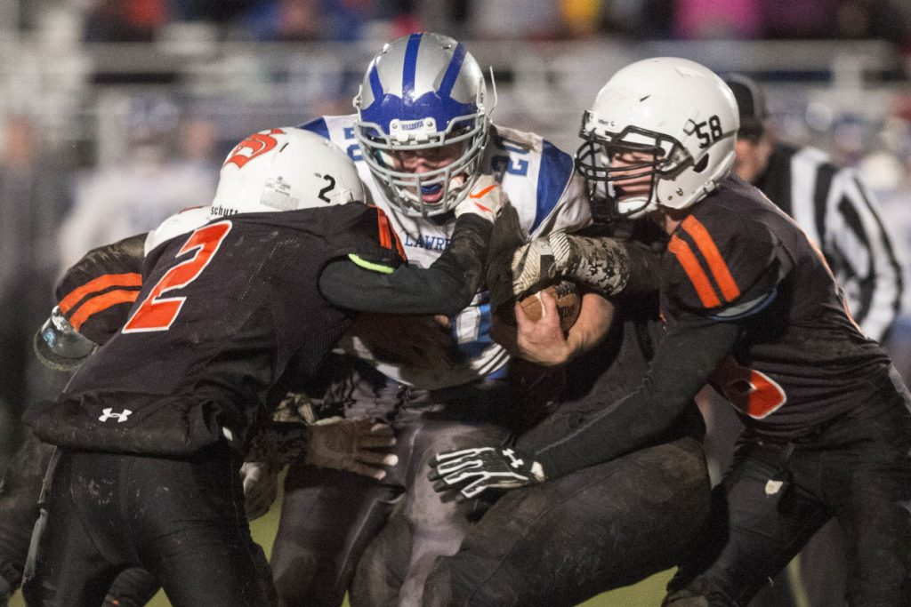 Lawrence's Kyle Carpenter, middle, gets tackled by Skowhegan defenders Spencer Wyman (2) and Chase Carey during a Pine Tree Conference Class B semifinal game Friday night in Skowhegan.