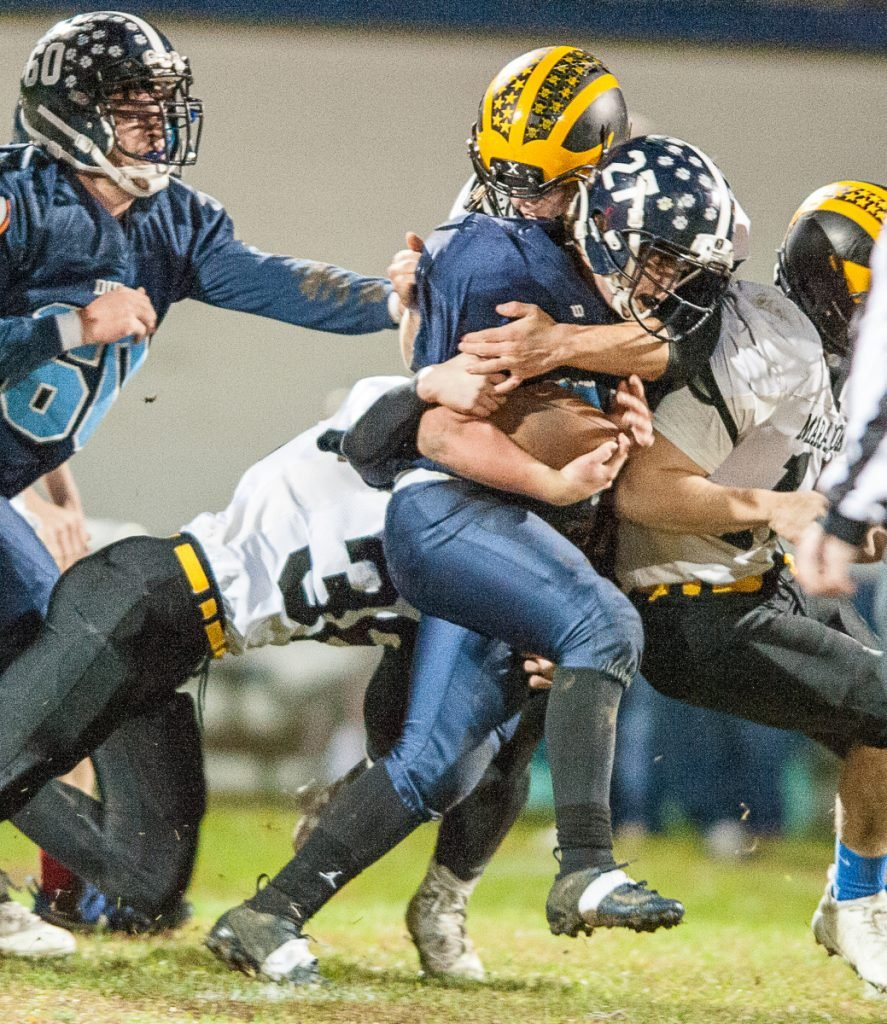 Maranacook's Joe Albert, left, assists teammates to bring down Dirigo's Dallas Berry during Friday night's Class E playoff game in Dixfield.