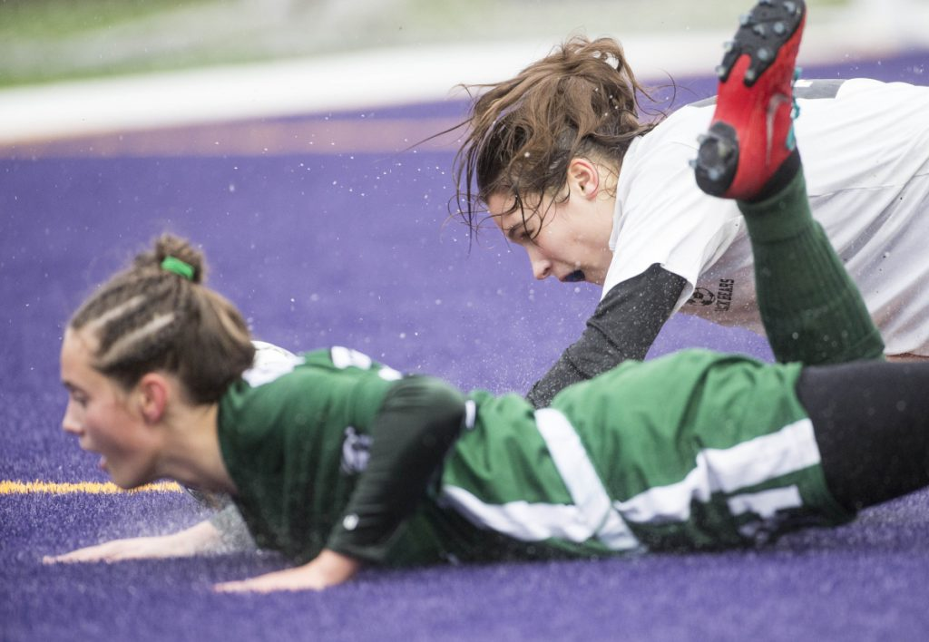 Fort Kent's Gabby Martin, left, gets knocked to the ground by Maranacook's Evelyn St. Germain in the Class C girls state championship game Saturday at Hampden Academy.