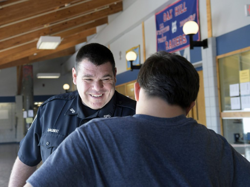 School resource officer John Dalbec confers with a buddy, Zachery Derosier, Oct. 10 in the lobby at Oak Hill High School in Wales. Dalbec said the best part of his job is speaking with students. Derosier is a junior.