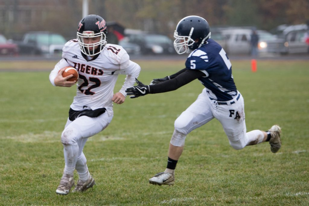 Gardiner's Cameron Michaud (22) carries the ball past Fryeburg's Dawsom Jones in a Class C South semifinal game Saturday at Fryeburg Acedemy.