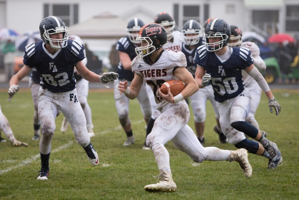 Gardiner's Garrett Maheux carries the ball past Fryeburg defenders Charlie Stokes (left) and Tucker Buzzell (right) in a Class C South semifinal game Saturday at Fryeburg Acedemy.