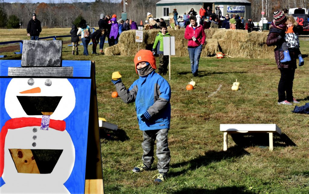 Joshua Dimartino takes aim with a bean bag at a snowman target during the Quarry Road Trails Fall Festival in Waterville on Sunday.
