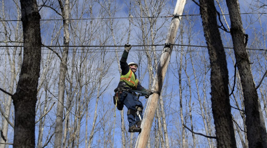 Central Maine Power lineman Sam Pottle scales a utility pole Sunday in Readfield. Pottle and his partner, George Marston, restored power at several locations in Kennebec County after wind knocked out service to 38,000 customers.