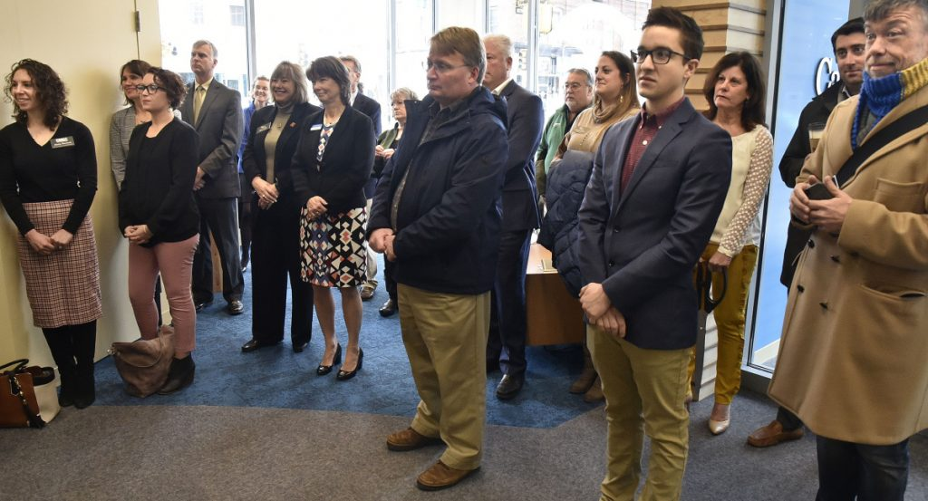 City and bank officials fill the lobby of the new Camden National Bank as speakers participate in a grand opening ceremony Monday in Waterville at the Bill & Joan Alfond Main Street Commons building.