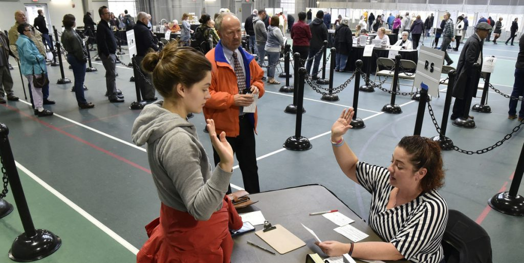 Colby College student Alexandria Fraize, left, swears the information she gave election clerk Allison Brochu is accurate before voting at Thomas College on Election Day as City Solicitor Bill Lee looks on.