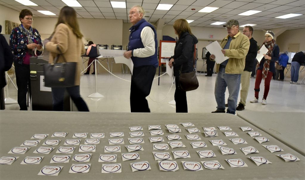 Winslow voters stand in line to cast ballots alongside a table full of voting stickers Tuesday at the Winslow VFW hall.