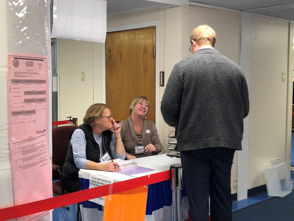 Deputy election clerks Julie Finley, left, and Traci Britten speak with a China voter on Tuesday night.
