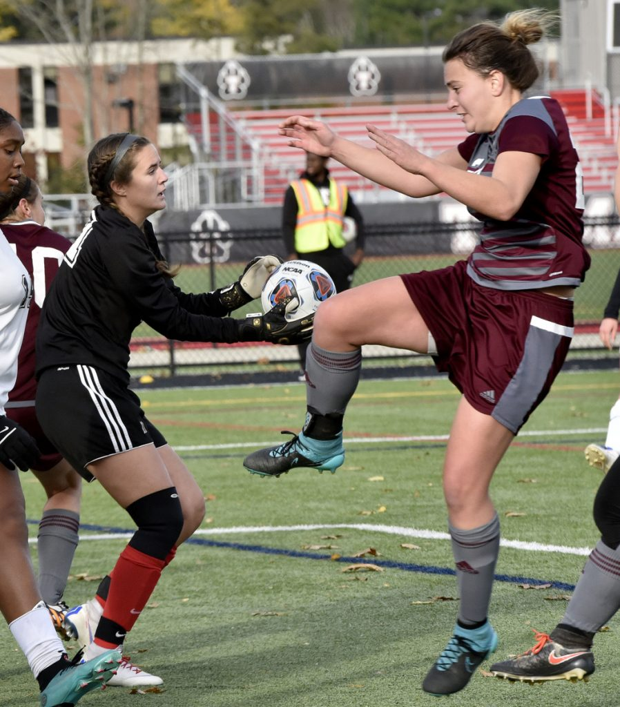 Thomas keeper Kayla Gordon, left, makes a safe as UMF's Hadley Yescott pressures her in the North Atlantic Conference championship game Sunday in Waterville.