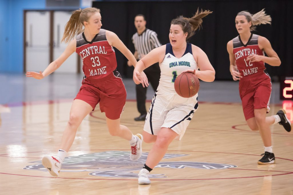 University of Maine at Augusta's Catherine Sanborn, middle, pushes the ball down the court while Central Maine Community College defender Ahna McCusker tries to keep pace during a game Tuesday night at the Augusta Civic Center.