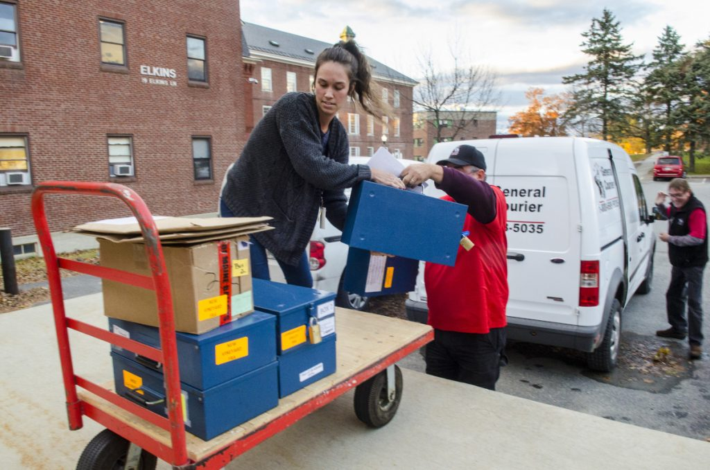 Department of the Secretary of State employees and courier service drivers take ballots out of vans and into the Elkins Building on Thursday in Augusta. The ranked choice voting counting is expected begin there at 9 a.m. Friday.