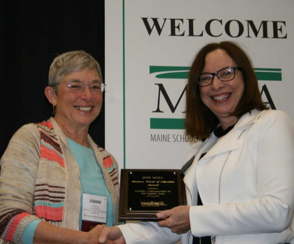Healthy Communities Executive Director Joanne Joy, left, accepts the Maine School Boards Association Business Friend of Education Award from MSBA President Maureen King.