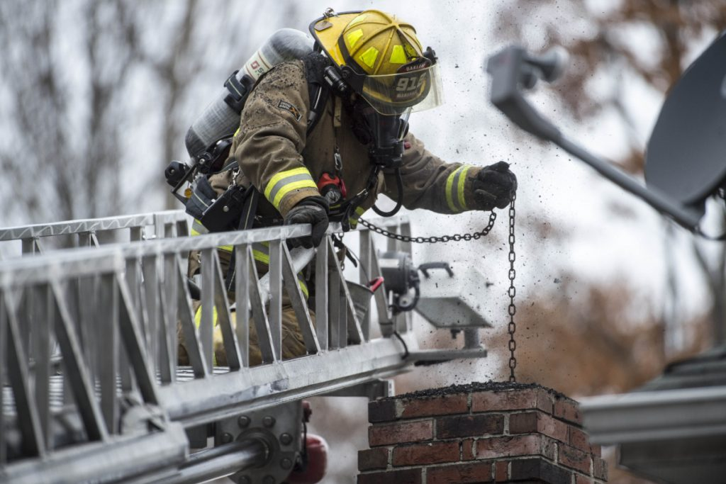 Oakland firefighter Randy Marshall extinguishes a chimney fire Friday at a residence on Mayland Street in Oakland. According to the Oakland Fire Department, residents should check their chimneys regularly, especially if wood is being burned.