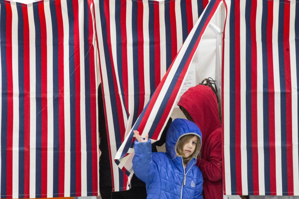 Alianna Shipley, 5, peers out from the voting booth that she is sharing with her brother Carter Hegarty, 8, and mother Jessica Lyon-Shipley at the Public Safety Building in Newport on Tuesday.