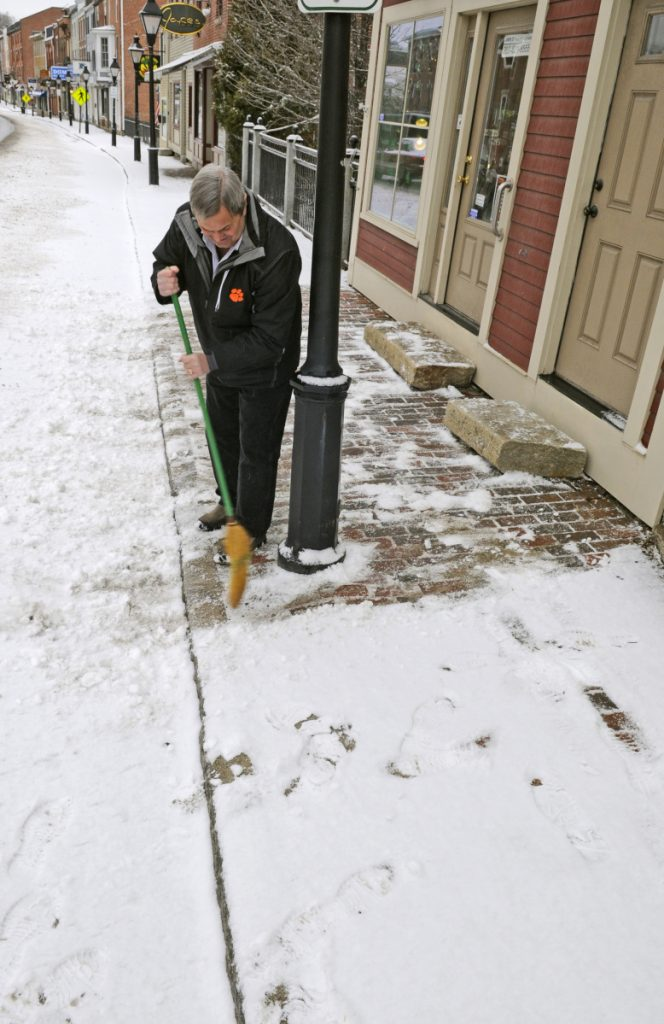 Jack Turner sweeps snow from from the sidewalk in front of his jewelry shop March 7, 2017, in downtown Hallowell. The City Council is considering a proposed ordinance that would require downtown-area commercial property owners to clear snow from the sidewalks in front of their buildings.