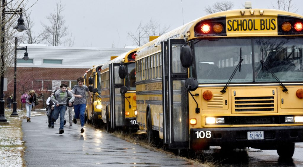 Messalonskee Middle School students run on Tuesday to a line of buses parked outside the school in Oakland. A grant resulting from a Volkswagen settlement with the U.S. government will help pay for two propane-fueled buses that RSU 18 plans to acquire.