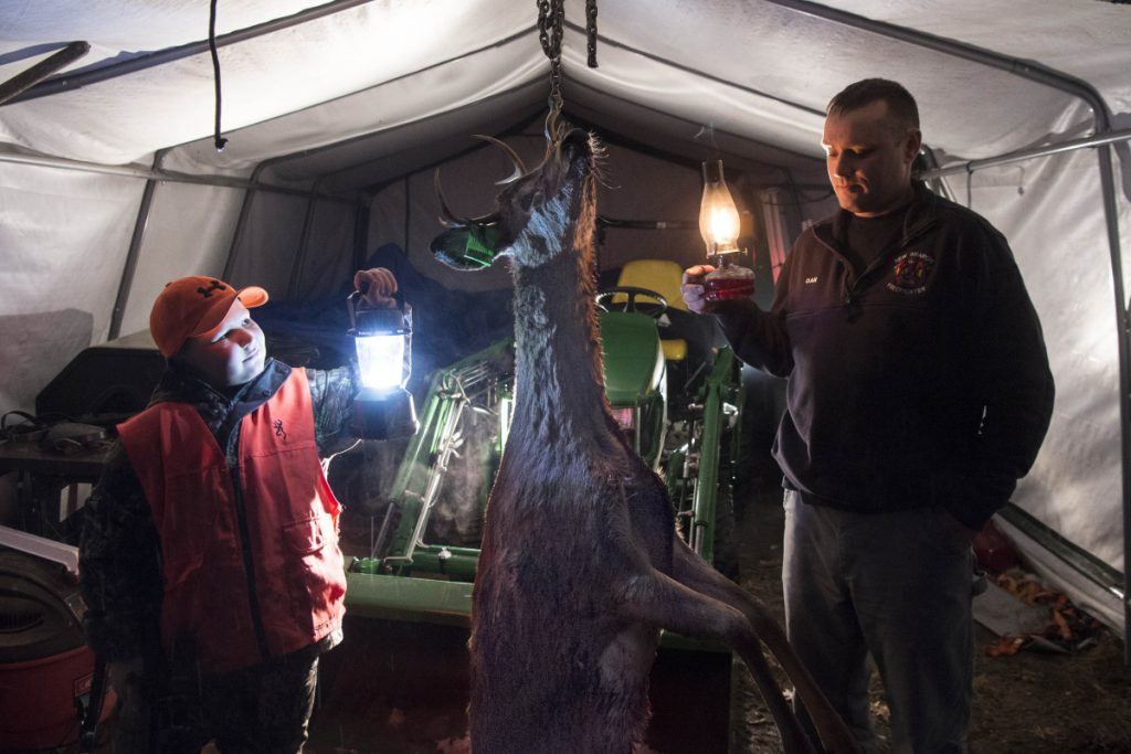 Chase Foss, 9, left, and his father, Daniel Foss, stand with a doe with antlers, a rare find, on Tuesday night at their home in New Sharon. Chase Foss bagged the deer on his first day of hunting on Monday with his father in Solon.