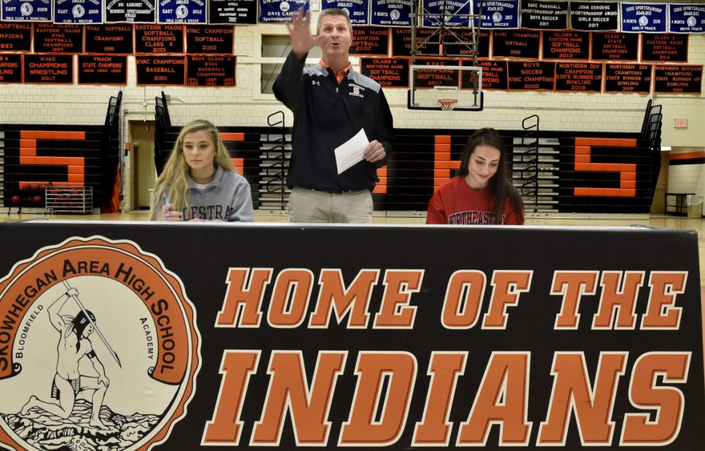 Skowhegan athletic director Jon Christopher, center, praises field hockey players Lizzie York, left, and Maliea Kelso, who signed letters of intent to play for Division I colleges Wednesday in Skowhegan.
