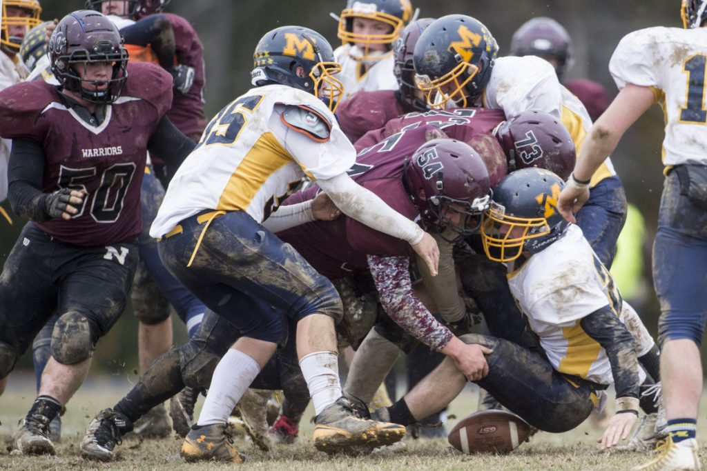 Medomak Valley's Drew Severson (24) fumbles the ball as he is hit by Nokomis' John  Tucker (73) and Phenyx Hatch last month in Newport.