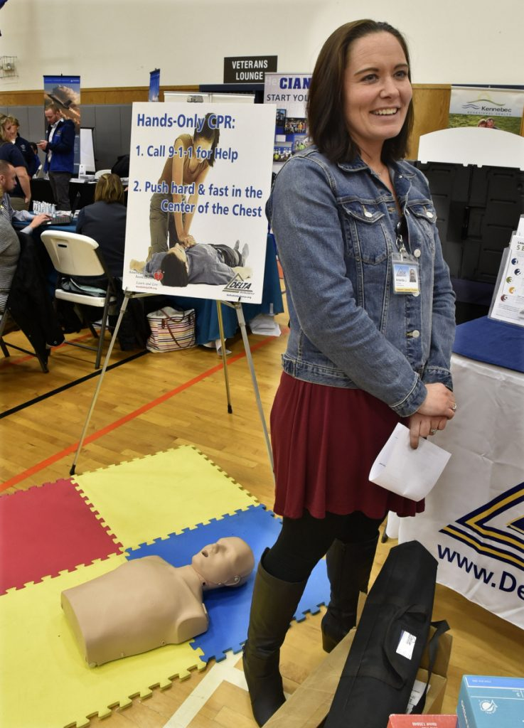 With a mannequin of a CPR patient as backdrop, Amanda Johnson, of Delta Ambulance, talks on Thursday about the need for more personnel during a job fair held at Kennebec Valley Community College's Hinckley campus.